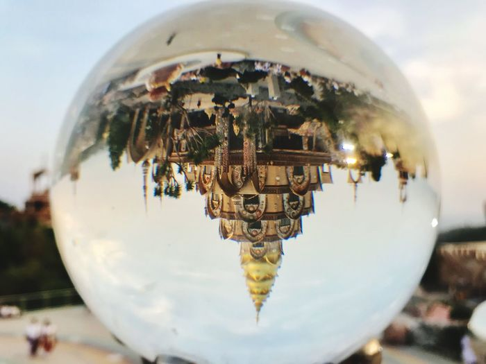 Close-up of crystal ball against sky seen through glass