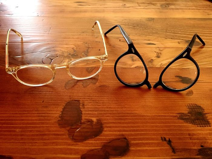 Eyeglasses with another broken eyeglasses on table