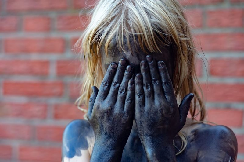 Girl Covered In Powder Paint While Hiding Face Against Brick Wall