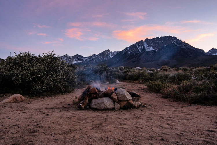 Campfire flames in stone firepit in desert at base of mountain at sunset