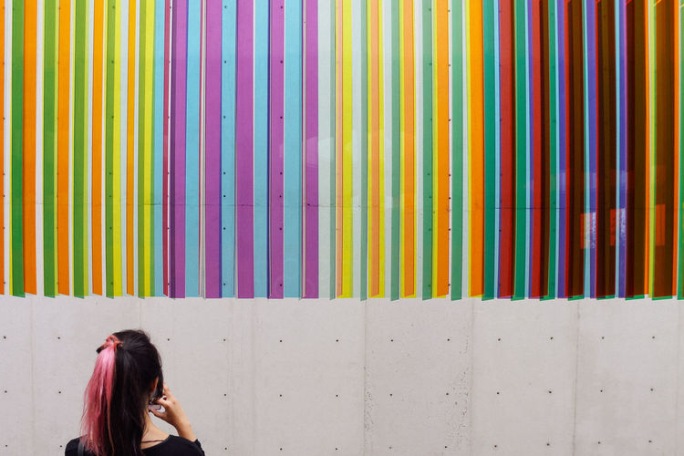 Rear view of woman looking at colorful patterned wall