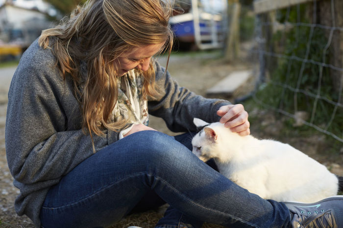A young woman plays with a cat on a farm Bonding Casual Clothing Cat Domestic Animals Farm Fence Friendship Girl Ireland Jeans Love One Animal Outdoors Pets Petting Real People Rural Sunset White Cat Woman Young Woman Young Women