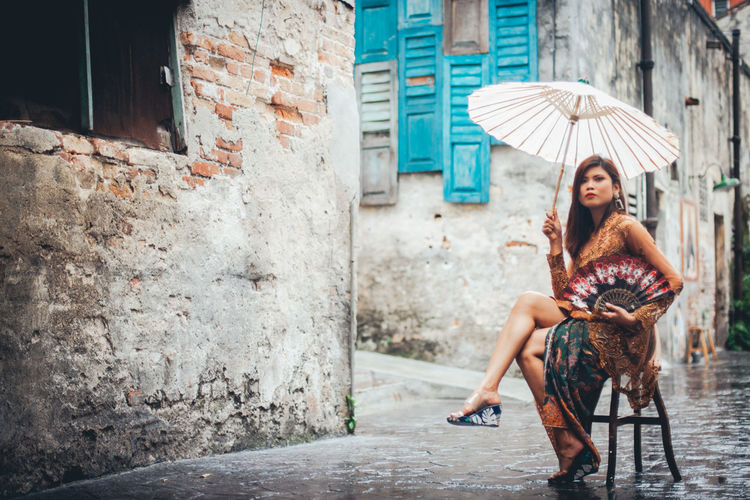 Full length of beautiful woman with umbrella sitting on stool in old town