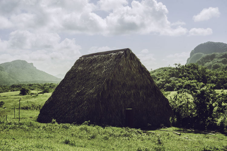Hut On Grassy Field Against Cloudy Sky