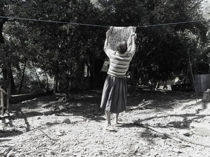 Rear view of woman drying clothes in yard