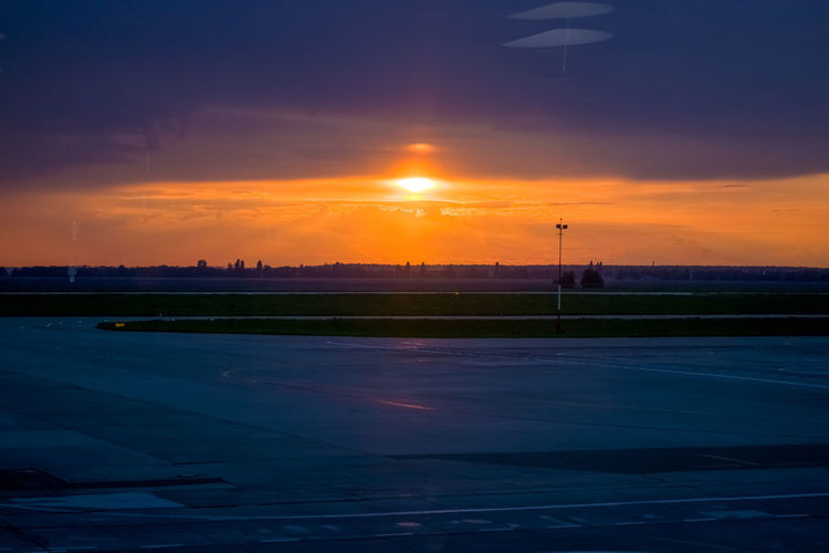 Sunset Sky Cloud - Sky Orange Color Nature No People Scenics - Nature Sun Beauty In Nature Airport Transportation Outdoors Road Airplane Sunlight Airport Runway Air Vehicle Street Tranquility Environment