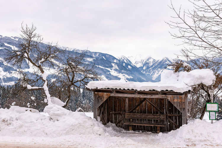 Old, wooden ski bus stop. snow covered mountains and field against sky. austria
