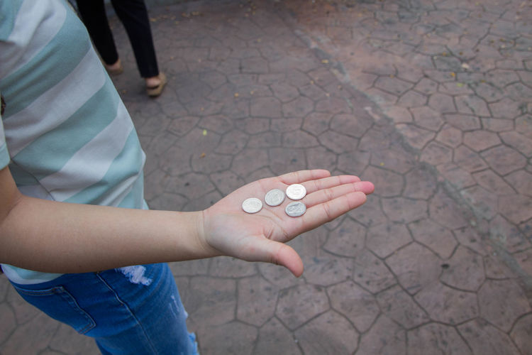 Midsection of woman holding coins on footpath