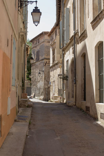 A narrow street at Arles, France Alley Architecture Building Exterior Built Structure City City Life Day Electric Light Empty Road Footpath Lamp Post Narrow No People Outdoors Residential Building Residential District Sky Street Street Light The Way Forward Tourism Travel Destinations