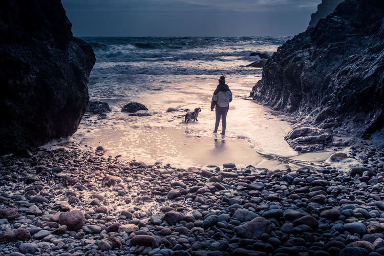 Throw my ball!! Moody seas at Kynance Cove Cornwall Bad Weather Beach Beauty In Nature Day Full Length Horizon Over Water Leisure Activity Moody Nature One Person Outdoors Pebble Beach People Real People Rock - Object Scenics Sea Sky Standing Sunset Walking Water Wave
