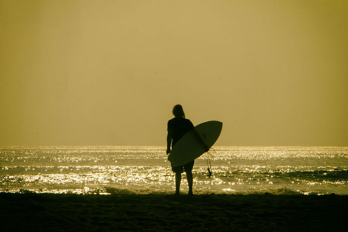 A surfers watches the sunset from the shore of the beach. Nexpa Surfer Beach Beauty In Nature Clear Sky Day Full Length Holding Horizon Over Water Leisure Activity Lifestyles Men Nature One Person Outdoors People Real People Scenics Sea Silhouette Sky Standing Sunset Water Wave An Eye For Travel