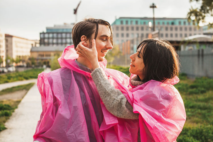 Couple in love wearing one piece two people poncho after the rain Couple Date Pink Rain Rainy Days Romancatholic Romantic Suit Affectionate Closeness Coat Conceptual Day Love Outdoors Park Pink Color Playful Poncho Relationshipsandstuff Smiling Summer Togetherness Toggether Two People