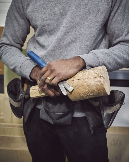Midsection of carpenter holding wood and chisel