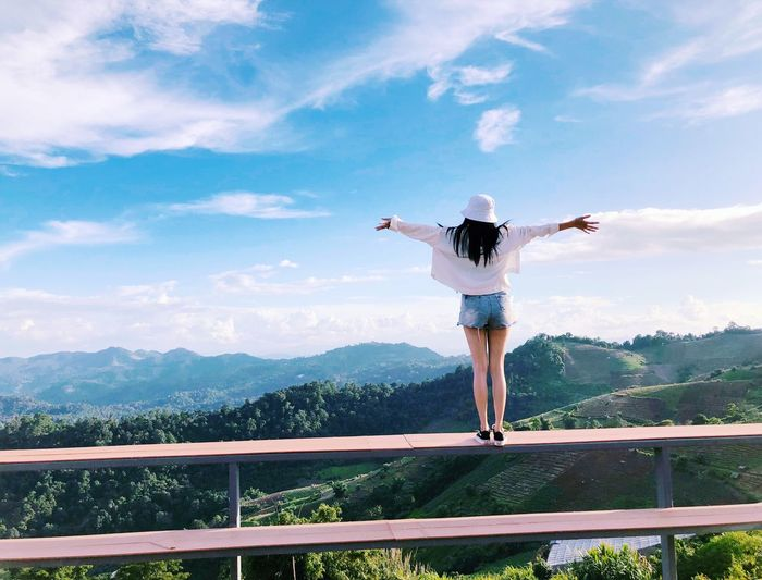 Rear View Of Woman With Arms Outstretched Standing On Railing By Mountains