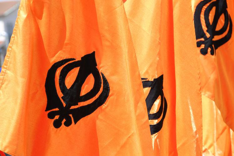 symbol of the Sikh religion called KHANDA formed by two scimitars on orange background Indian Indian Ocean Indian Culture  Orange Punjab Sikhi Backgrounds Emblem  Indian Style Khanda Khanda Flag Kirpan Nagar Nagar Kirtan Nagarkirtan  Punjab India Punjabi Religion Architecture Scimitars Sikh Sikh Theme Sikhism Sikhlife Sikhs Symbol