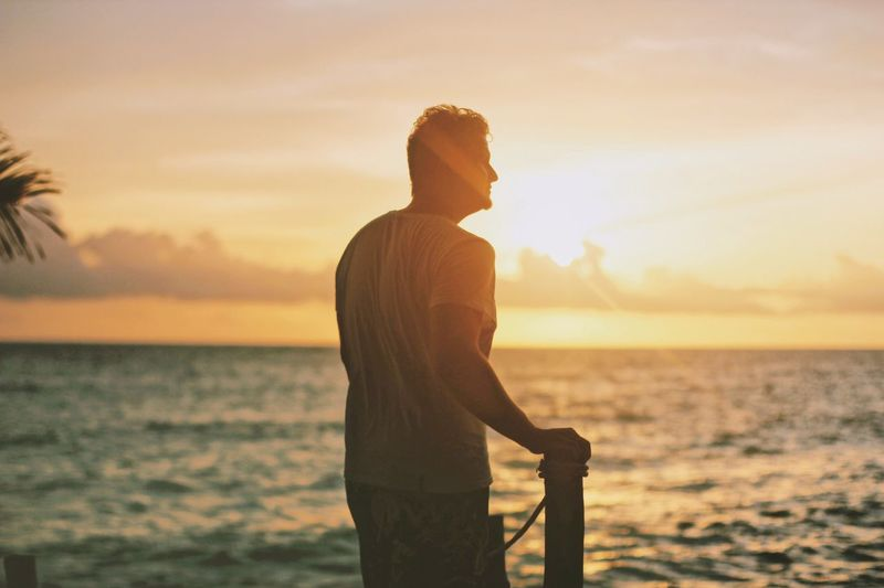 Rear view of young man looking at sea while standing against sky during sunset