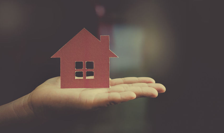 Close-up of hand holding small house against building
