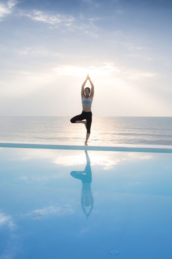Full length of mature woman practicing yoga at poolside against sea and sky