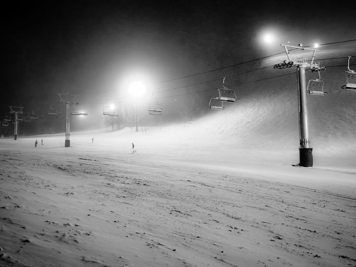 Street lights on snow covered field at night