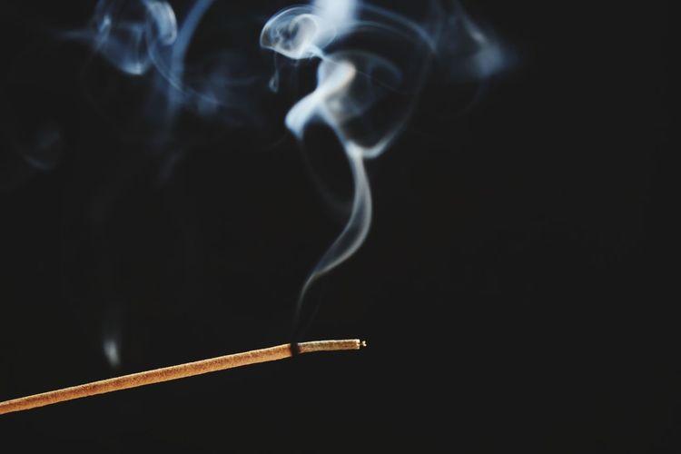 Close-up of incense stick against black background