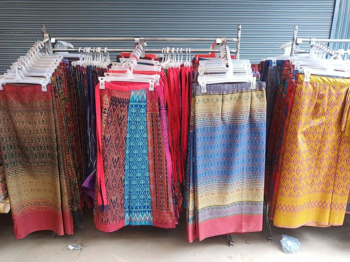 Multi colored clothes hanging in store