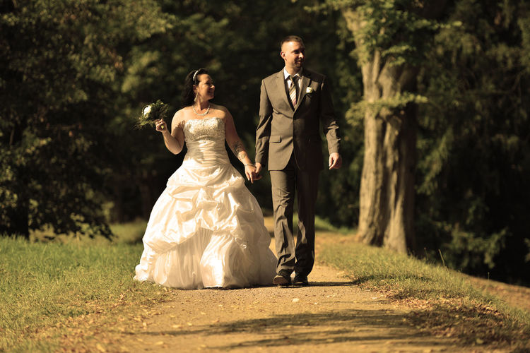 Full Length Of Newly Wed Couple Walking On Field In Park