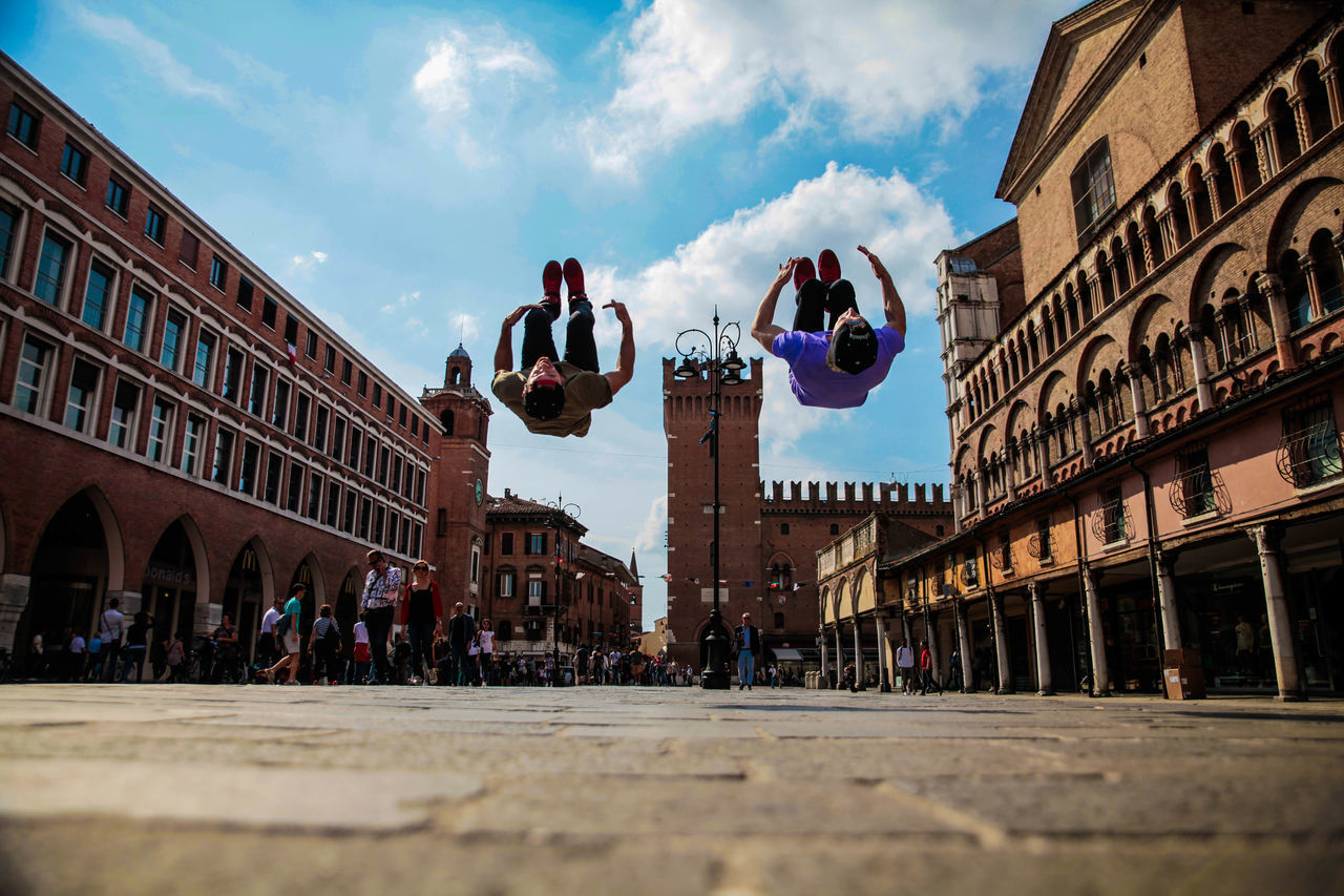 Surface Level Shot Of Men Backflipping On Street Outside Ferrara Cathedral
