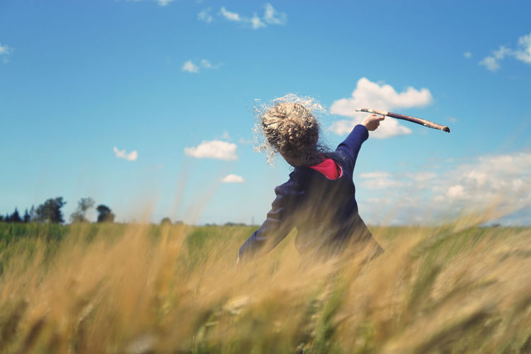 Rear view of girl throwing stick against sky