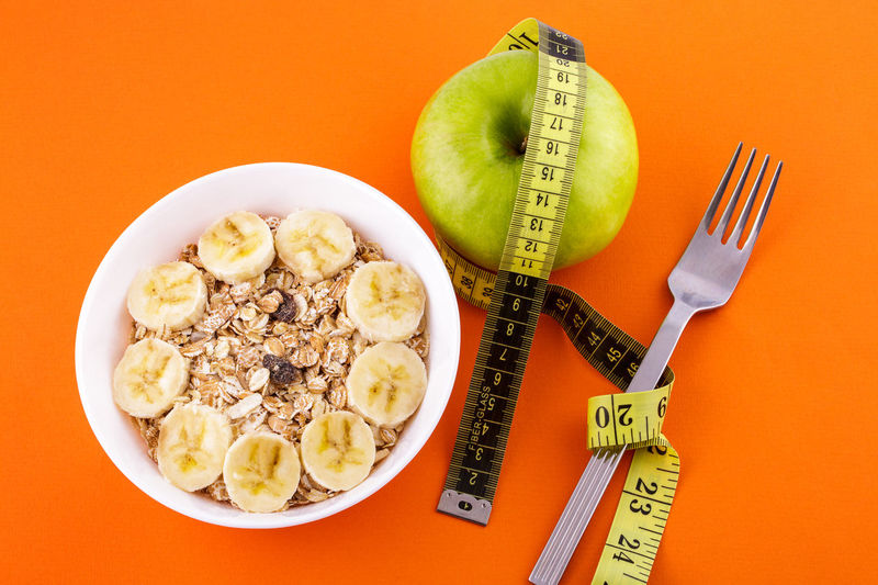 Muesli with banana on orange background with apple and measuring tape