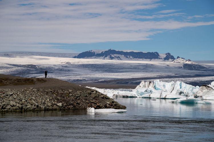 Person standing on mountain at jokulsarlon glacial lagoon
