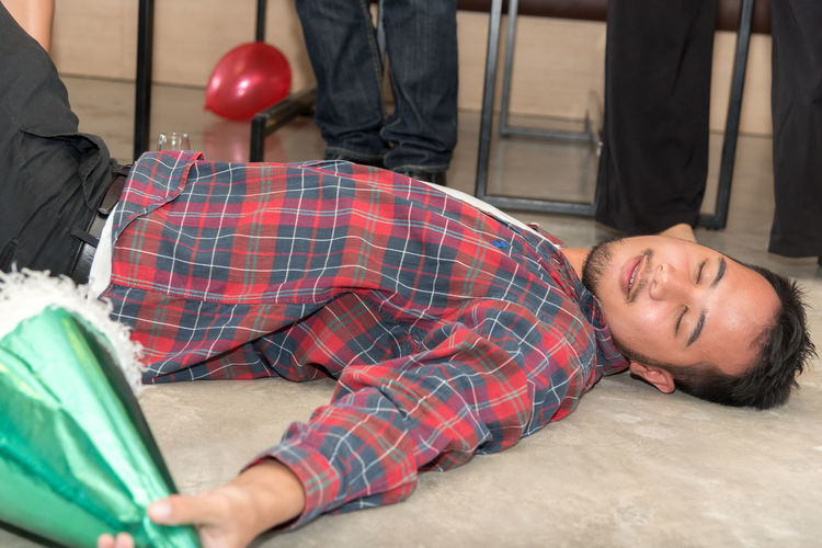Drunk man lying on floor during party