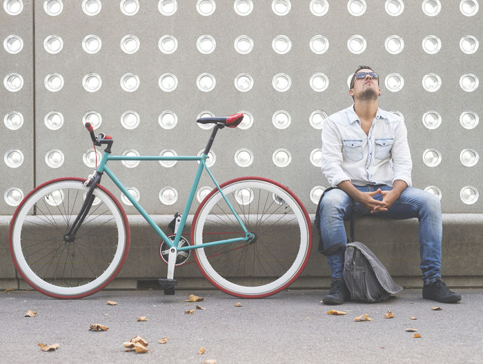 Full length of a man sitting with bicycle