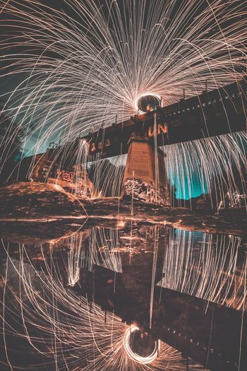 Long Exposure Night Motion Spinning Illuminated Wire Wool Reflection Light Trail Firework - Man Made Object Water Outdoors Firework No People Sky