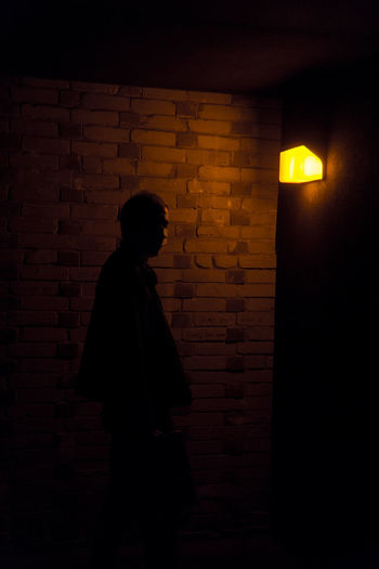 Silhouette man standing against illuminated wall