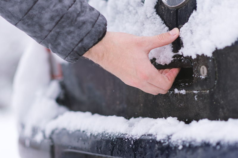 Cropped hand of man opening car trunk door during winter