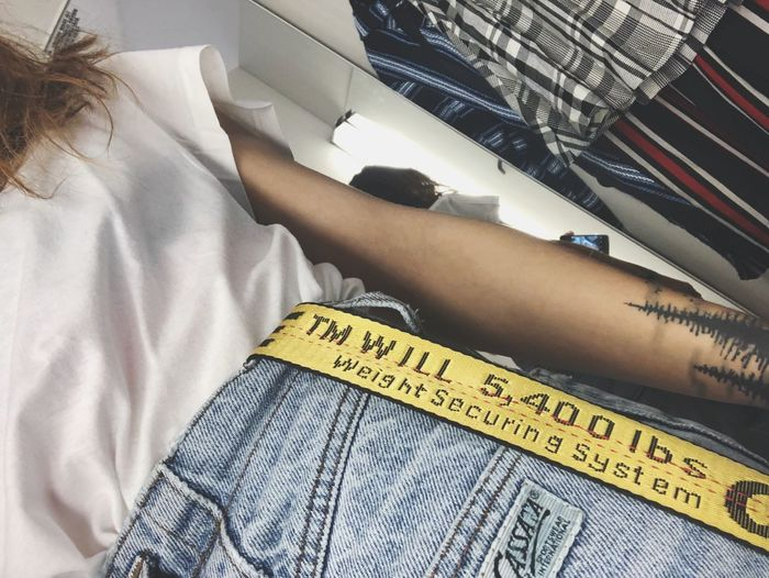 Blue jeans, white shirt, yellow off white belt. High Fashion Belt  White Shirt Blue Jeans Offwhite Quality Forest Tattoo Indoors  High Angle View One Person Day Close-up People