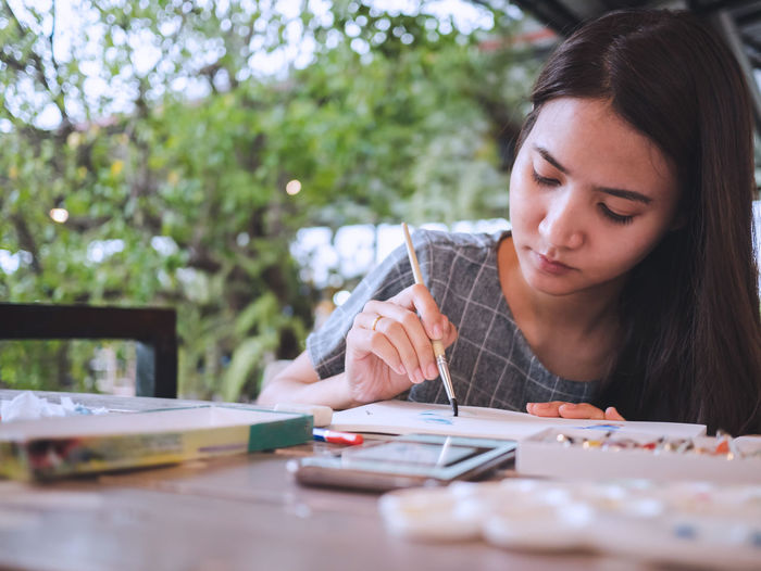 Girl painting on paper over table