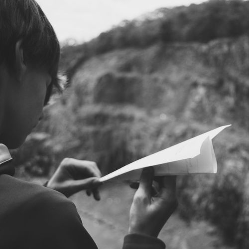 Cropped image of boy holding paper airplane