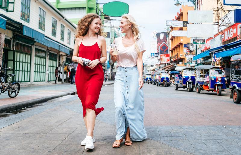 Friends walking on street in city