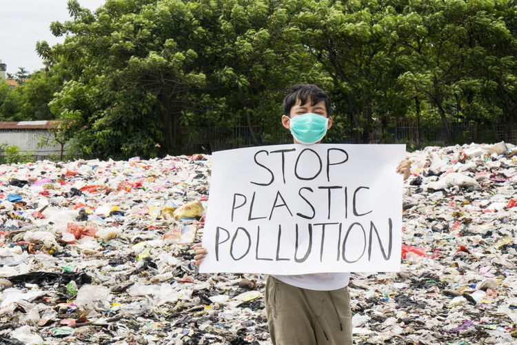 Portrait of boy holding poster against plastic garbage