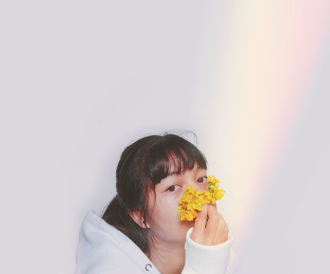 Portrait of woman holding yellow flower against white wall