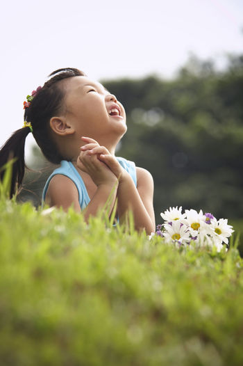 Girl With Bunch Of Flowers Lying On Grassy Field At Park