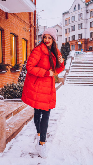 Beautiful happy smiling woman on the street in warm red winter coat on Christmas time on snowing. Winter Cold Temperature Warm Clothing Snowing Smiling Christmas Wintertime Woman Power women around the world EyeEm Best Shots EyeEm Colorful! Fashion Stories Red Lipstick Architecture Young Adult Real People Portrait Beautiful Woman Lifestyles Outdoors Scarf Standing Hairstyle