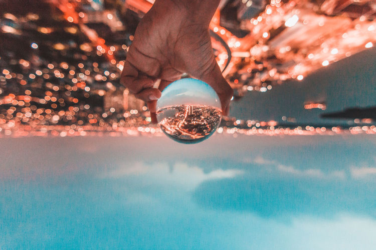 Reflection Human Body Part Hand Human Hand One Person Real People Glass - Material Transparent Lifestyles Nature Sphere Leisure Activity Water Body Part Focus On Foreground Unrecognizable Person Holding Illuminated Outdoors Finger Swimming Pool Surface Level