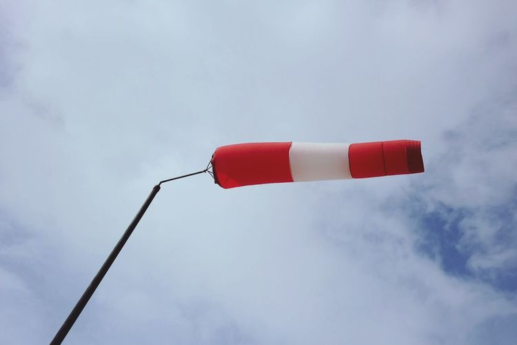 Low angle view of windsock flying against cloudy sky