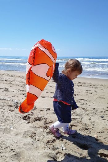 Cute girl with balloon walking at beach against sky