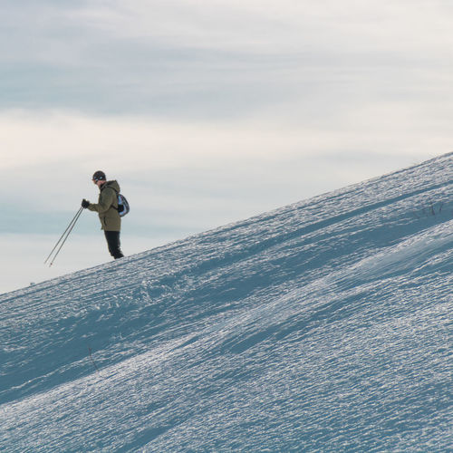 Side View Of Male Hiker Hiking On Snowcapped Mountain Against Cloudy Sky