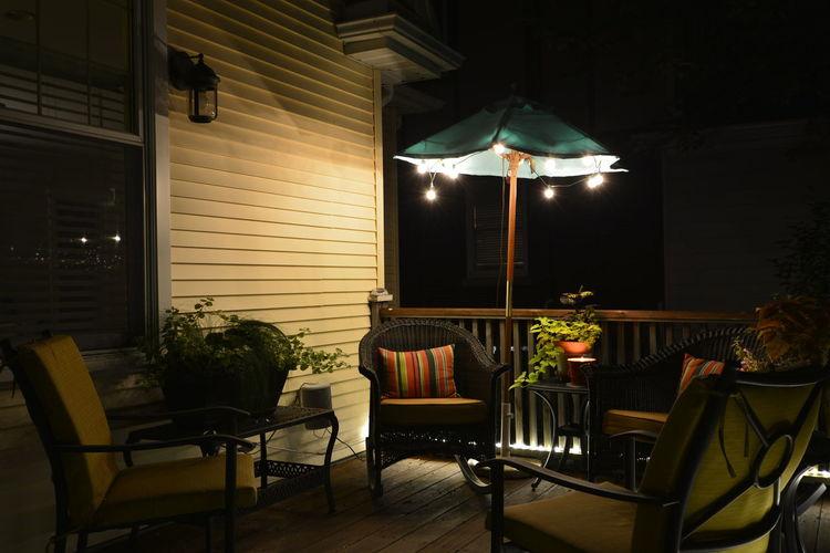 Furniture at illuminated patio during night
