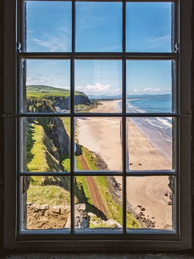 Scenic view of sea seen through glass window