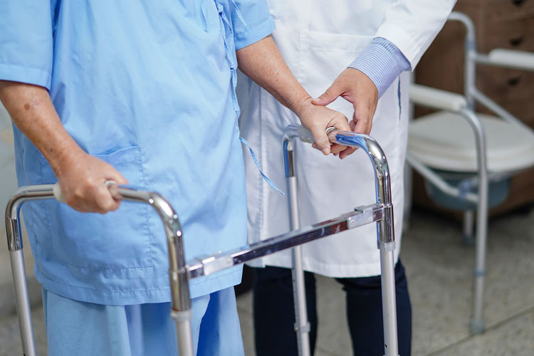 Midsection of doctor helping patient with walker